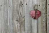 Key to my heart; red checkered (plaid) heart with brass skeleton key hanging on rustic wooden door