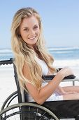 Wheelchair bound blonde smiling at the camera on the beach on a sunny day
