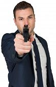 Serious businessman pointing a gun on white background