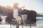 Beautiful blonde in white sundress on bike ride at the beach on a sunny day