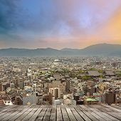 Sunset city scenery with wooden floor and buildings under dramatic sky, Kyoto, Japan, Asia.