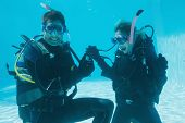 Man proposing marriage to his shocked girlfriend underwater in scuba gear on their holidays