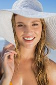 Beautiful girl in bikini and straw hat on the beach smiling at camera on a sunny day