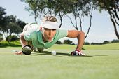 Female golfer blowing her ball on putting green on a sunny day at the golf course
