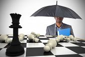 Composite image of businessman standing under umbrella with chessboard