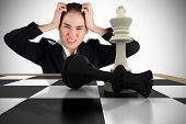 Stressed businesswoman with hands on her head with chessboard against white background with vignette