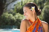 Brunette in sarong smiling by the pool outside at the spa