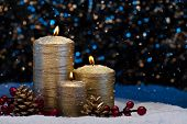 Three Gold Candles In Snow