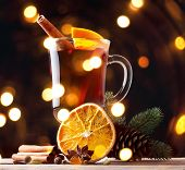 Mulled wine, blue pine tree branch and spices on wooden background