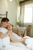 Amorous couple relaxing in bed in the morning