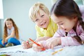 Cute little boy looking at camera while lying on the floor and drawing with his friends near by