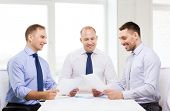 business and office concept - smiling businessmen with papers in office