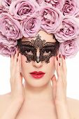 Portrait of young beautiful woman with fancy flower wig and venetian mask over white background