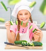 smiling little girl cuts cucumbers home in the kitchen