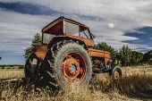 farming, old agricultural tractor abandoned in a farm field