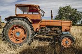 old agricultural tractor abandoned in a farm field