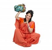 image of turban  - Caucasian mature woman in orange sari sitting and holds turban on white background