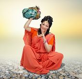 foto of turban  - Sitting Caucasian mature woman in orange sari posing with turban