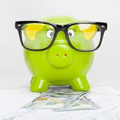 Green Piggy Bank Over Stock Market Chart With 100 Dollars Banknote