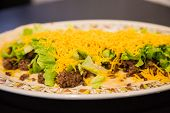 foto of shredded cheese  - Ground beef shredded lettuce and grated cheddar cheese on soft flour tortillas - JPG