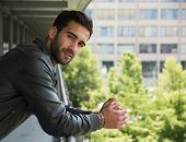 image of long beard  - Profile shot of attractive bearded young man in city looking at camera outdoors - JPG