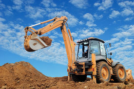 picture of backhoe  - Excavator Loader with rised backhoe standing in sandpit with over cloudscape sky - JPG