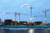 Construction Site Of  Residential Building, Tower Cranes With Evening Lights.
