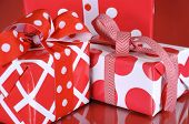 Stack Of Bright Red And White Polka Dot And Check Festive Christmas Gift Boxes On Red Background. Cl