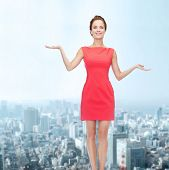 advertising, holidays and people concept - smiling young woman in red dress holding something on palm of her hands over city background
