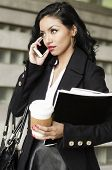 Beautiful busy young business woman talking on cell phone