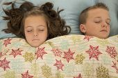 Two Cute Kids Asleep Under A Snowflake Blanket