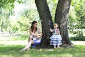 Beautiful mother and daughter blow bubbles in a city park.