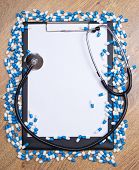 Heal Of Tablets, Clipboard And Stethoscope On Wooden Table