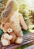 Little Girl Sitting Back With Teddy Bear On The Bench In Sun Beams Outside In The Park