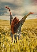 Young Red Hair Woman Standing Back Hands Up To Breathtaking View Of Dramatic Sunny Sky In The Field