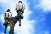 Old-fashioned Black And Gold Streetlamps Against Blue Sky
