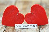 Feliz Cumpleanos (which means Happy Birthday in Spanish) with two red wooden hearts