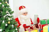 Confused Santa Claus Looking At Laptop Pc.