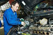 auto mechanic repairing automobile car engine turbine at maintenance repair service station garage