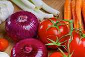 Red onion and tomatos on a wooden board