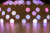 Abstract background of blurred purple and white color lights with bokeh effect