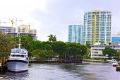 Miami suburb with residential buildings palms and marine transport.