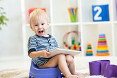 child sitting on chamber pot playing tablet pc