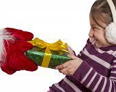 Little girl pulls Christmas gift of the hands of Santa