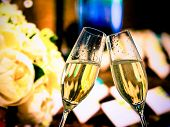 stock photo of flute  - champagne flutes with golden bubbles make cheers on wedding flowers background - JPG