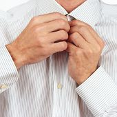 Hands a guy fastened collar of bright shirt closeup