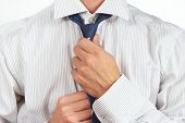 Guy tying his tie over bright shirt closeup