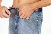 Shirtless guy buttons belt on his blue jeans closeup