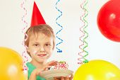 Little kid in holiday hat eating piece of birthday cake