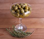 Green olives in oil with spices and rosemary in glass vase on wooden table